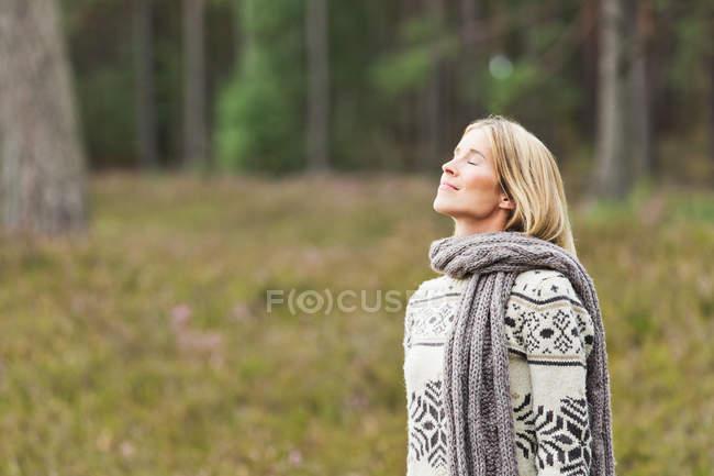 Mulher adulta média usando suéter com os olhos fechados — Fotografia de Stock