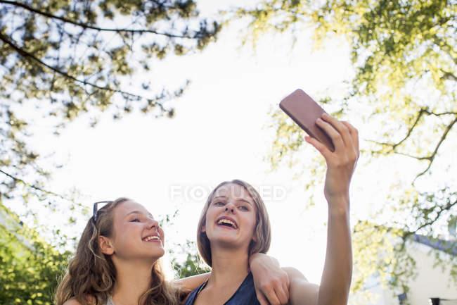 Deux adolescentes en parc en tenant le smartphone selfie — Photo de stock