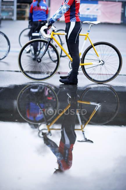 Jóvenes ciclistas adultos entrenando en la pista de velódromo - foto de stock