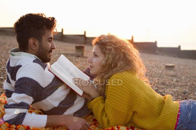 Pareja joven tumbada en la playa, mujer leyendo libro - foto de stock