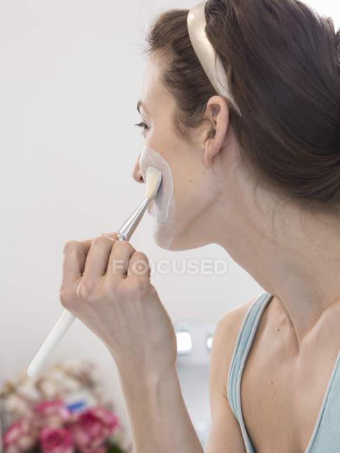 Mitte erwachsene Frau feuchtigkeitsspendende Gesicht mit Make-up-Pinsel — Stockfoto