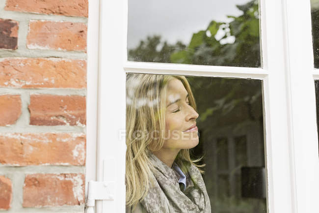 Mid adult woman by window with eyes closed, smiling — Stock Photo