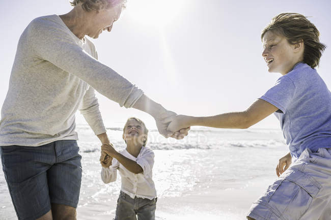 Father and sons playing on beach — Stock Photo