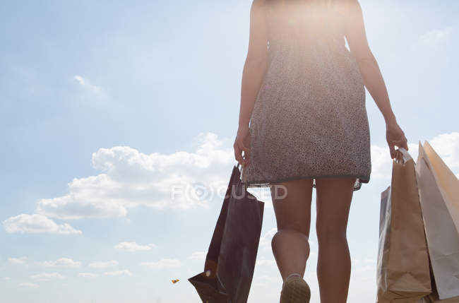 Mid section of woman carrying shopping bags — Stock Photo