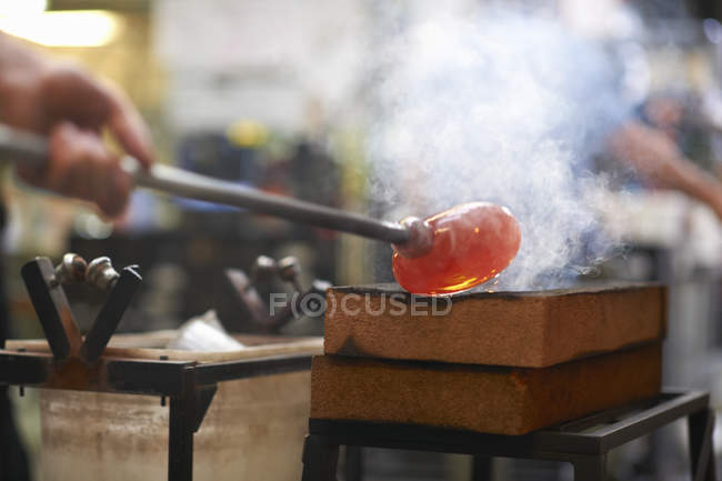 Molten glass material being shaped on blowpipe in workshop — Stock Photo