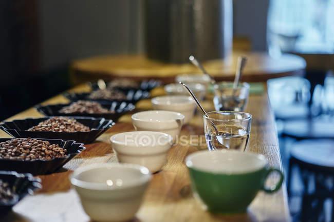 Chicchi di caffè, ciotole e tazze onwooden tabella con sfondo di messa a fuoco — Foto stock