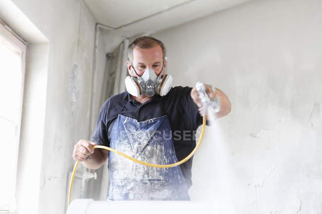 Hombre con máscara protectora pintura en aerosol madera - foto de stock