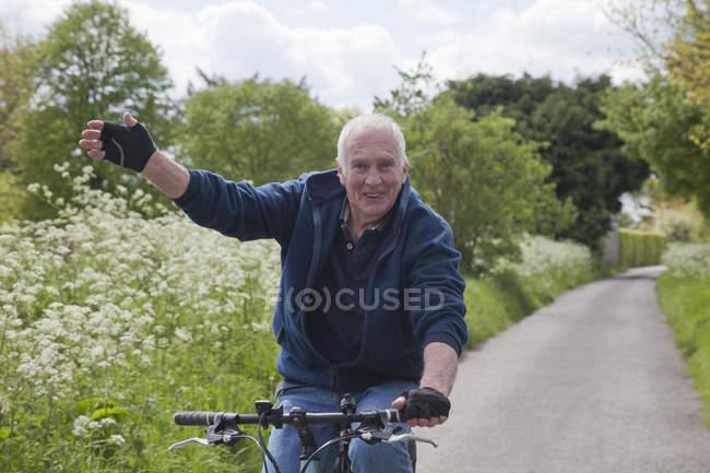 Старший на велосипеде по проселочной полосе — стоковое фото