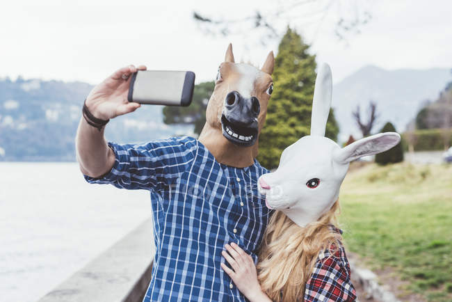 Couple wearing horse and rabbit masks taking smartphone selfie, Lake Como, Italy — Stock Photo