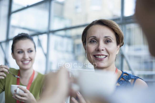 Женщины-коллеги по бизнесу делают перерыв на кофе в офисе — стоковое фото