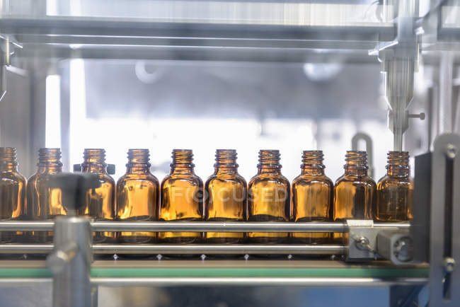 Glass bottles in row at pharmaceutical factory — Stock Photo