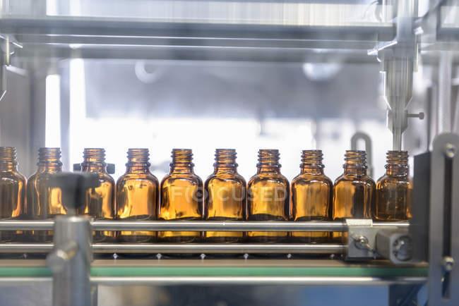 Bottiglie di vetro in fila in fabbrica farmaceutica — Foto stock