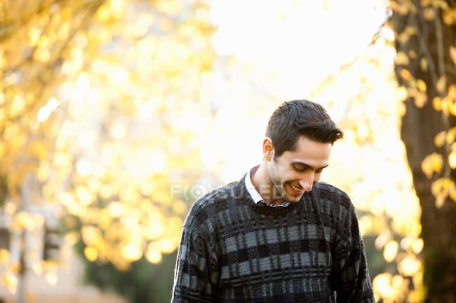 Junger Mann blickt in sonnenbeschienenen Park und lächelt — Stockfoto