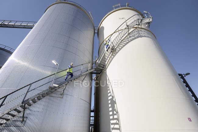 Low angle view of workers climbing oil storage tanks in oil blending factory — Stock Photo