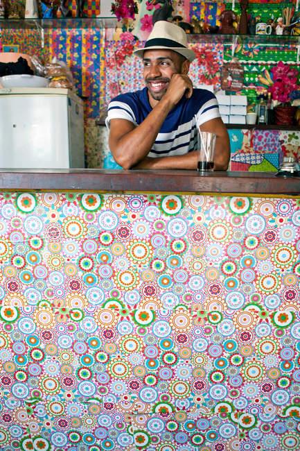 Людина, що спирається на лічильник кафе-бару — стокове фото