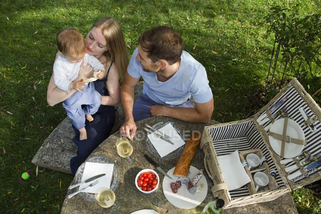 Overhead-Ansicht von mittleren erwachsenen Paar und Baby-Tochter sitzt am Picknicktisch im Garten — Stockfoto
