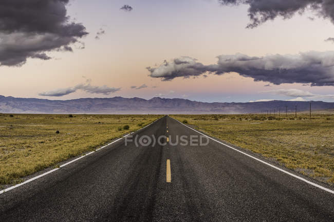 Diminishing perspective view of straight road at sunset — Stock Photo