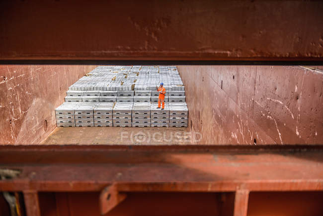 Worker checking metal ingots in ship's hold — Stock Photo