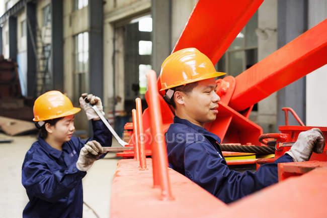 Trabalhadores que utilizam equipamentos em instalações de fabricação de guindastes, China — Fotografia de Stock