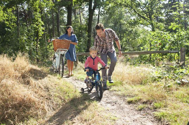Familie radelt durch Wald — Stockfoto