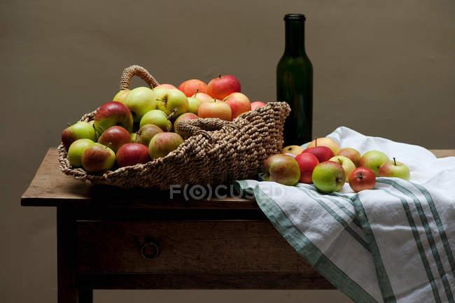 Korb mit Äpfeln und Wein auf Tisch — Stockfoto