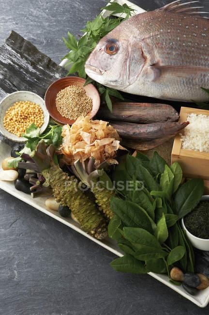 Prato de alimentos, incluindo peixe e produtos hortícolas frescos — Fotografia de Stock