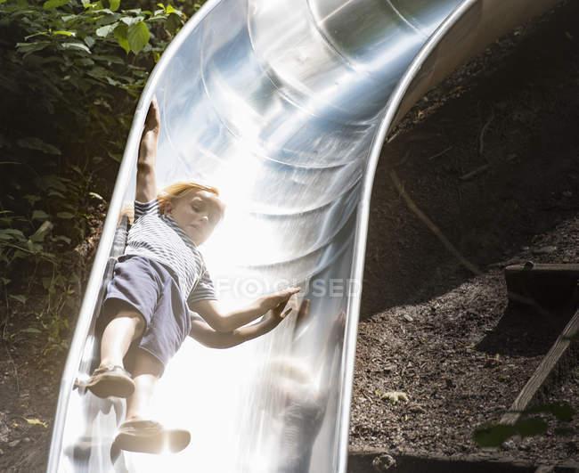 Junge rutscht Spielplatzrutsche hinunter — Stockfoto