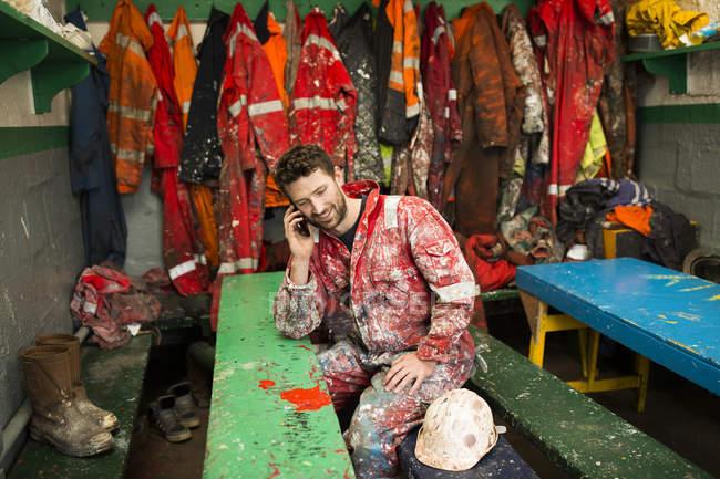 Чоловічий корабель художник, сидячи в сараї говорити на смартфоні — стокове фото