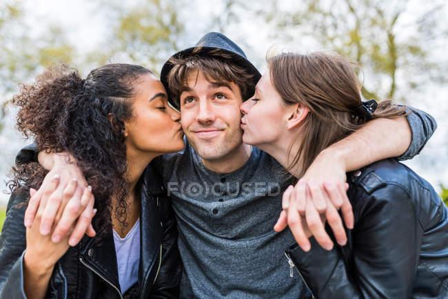 Glücklicher Mann und zwei Frauen küssen sein Gesicht, küssen die Wangen — Stockfoto
