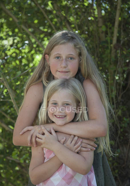 Blonde sisters with arms around standing outdoors in park — Stock Photo