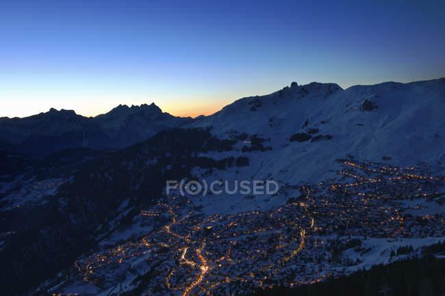 Ville éclairée sous la chaîne de montagnes la nuit — Photo de stock