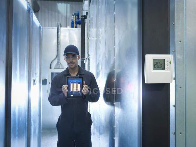 Гордый работник завода показывает энергосбережение на цифровых планшетах на заводе, портрет — стоковое фото