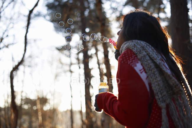Mujer madura que sopla burbujas en bosque - foto de stock