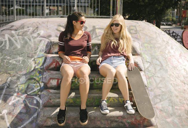 Две подруги скейтбординга чате в скейтпарк — стоковое фото