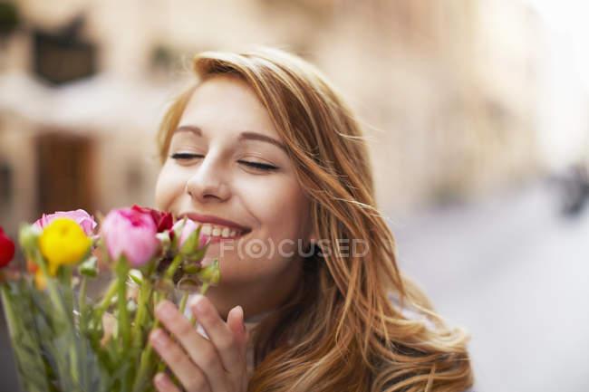 Улыбается молодой женщины, пахнущий букет цветов — стоковое фото