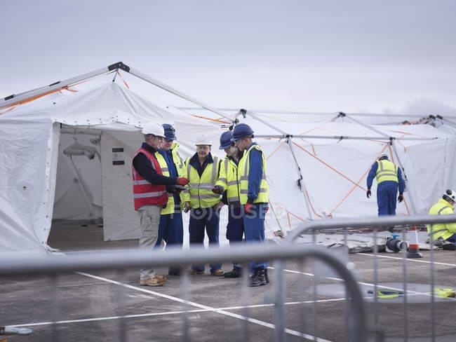 Сотрудники аварийно-спасательной группы обучающиеся в палатке центра управления — стоковое фото