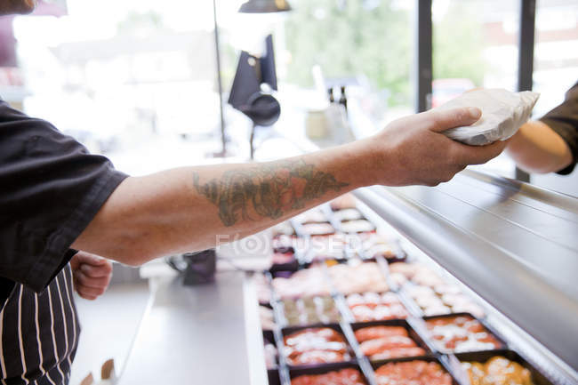 Cropped shot of butcher handing produce to customer in butchers shop — Stock Photo