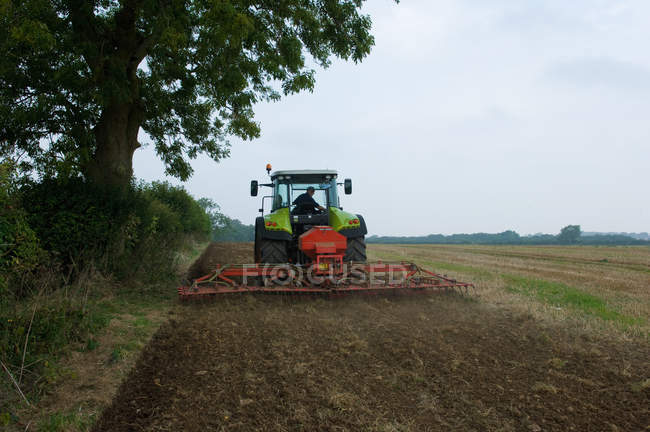 Farmer driving tractor and planting seeds of corn in field — Stock Photo