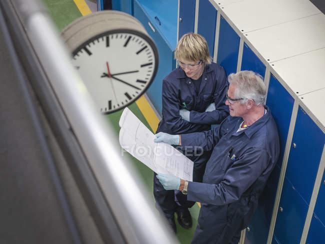 Ingeniero senior instruyendo aprendiz en fábrica, vista de ángulo alto - foto de stock