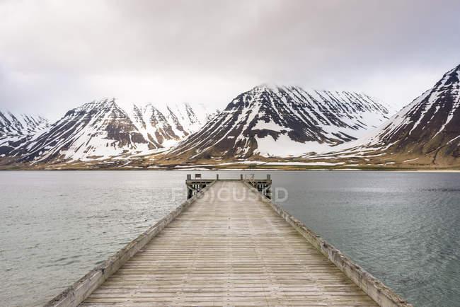 Vista in prospettiva del molo di legno con montagne innevate sullo sfondo di diminuzione — Foto stock