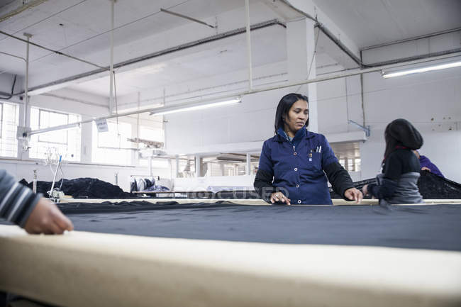 Factory workers unrolling textiles on work table in clothing factory — Stock Photo