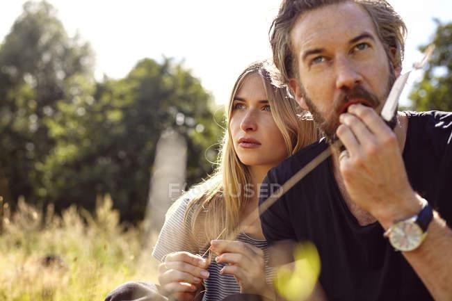 Coppia mangiare mentre seduto in campo rurale — Foto stock