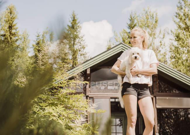 Жінка в саду, несучи Котон де тулеар собака, Orivesi, Фінляндія — стокове фото