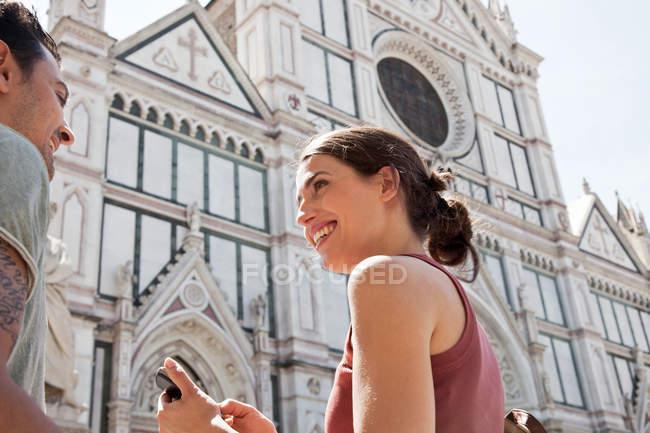 Мужчина и женщина у церкви Санта Кроче, площадь Санта Кроче, Флоренция, Тоскана, Италия — стоковое фото