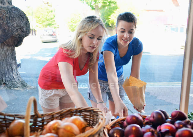 Two young women choosing food at market stall — Stock Photo