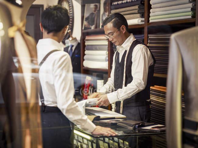Отец и сын рассматривают ткань в семейном магазине портных — стоковое фото