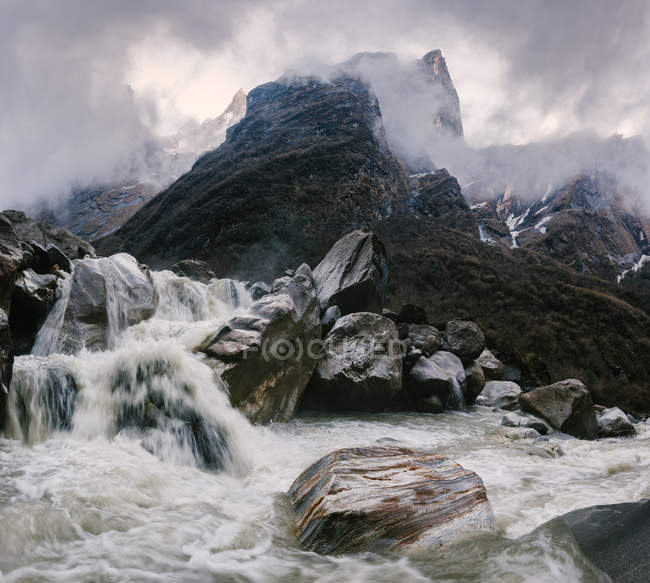 Motion blurred water flowing down misty rocks — Stock Photo