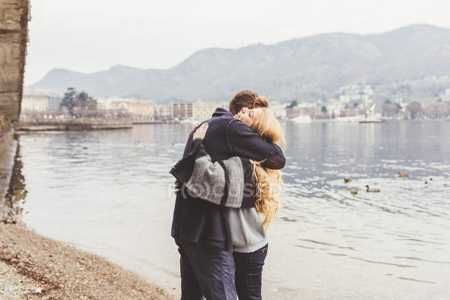 Young couple hugging each other on lakeside, Lake Como, Italy — Stock Photo