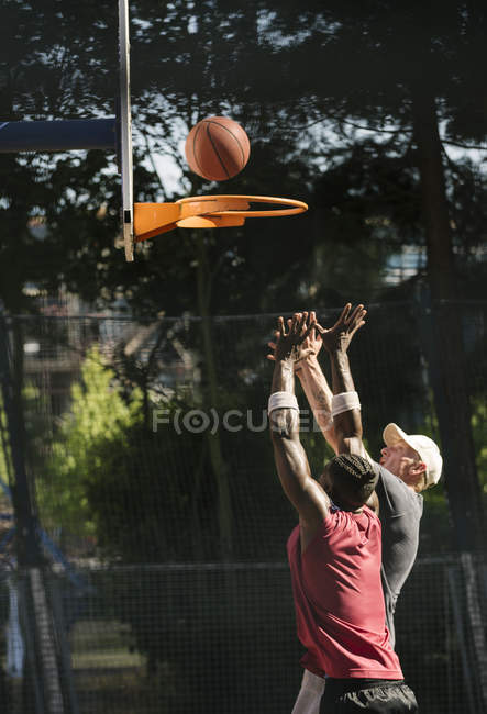 Young male basketball players throwing ball at basketball hoop — Stock Photo