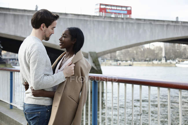 Couple standing by river, face to face, man putting coat around woman's shoulders — Stock Photo